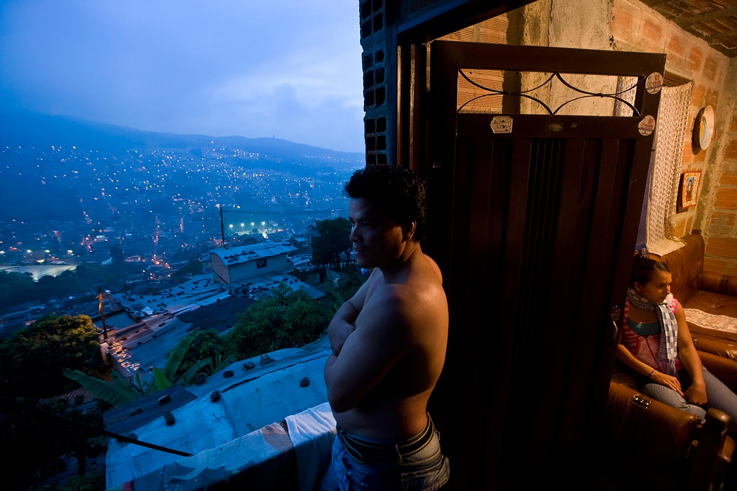 NIGHT IS FALLING A displaced man looks at the view of 'Esfuerzos De Paz #1' neighborhood in Medellin as night falls. The nighttime is extremely dangerous in neighborhoods populated by displaced families being the preferred time for guerrilla or the paramilitary militants to operate.