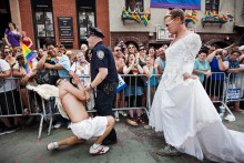 A couple wearing sailor and nurse outfits kiss during the annual Pride Parade in a homage to the famous picture from Times Square in 1945 that symbolizes the end of World War II.
